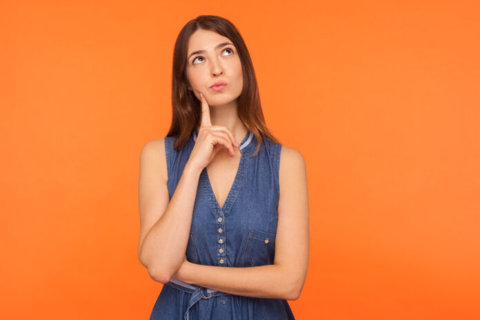 Pensive brunette woman in denim dress looking up with thoughtful doubtful expression, pondering serious difficult idea, imagination and vision in mind. indoor studio shot isolated on orange background
