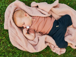 Portret słodkiego dziecka bawiącego się na zewnątrz, dziecko korzystające ze świeżego powietrza na kocu w ogrodzie lub parku