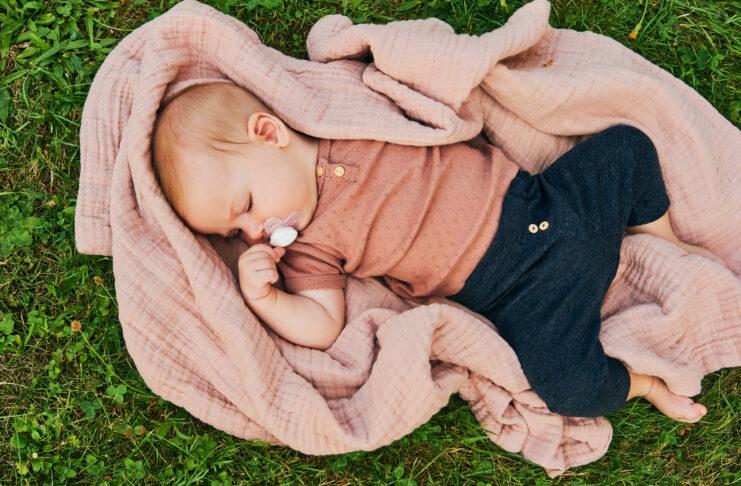 Porträt eines süßen Babys, das draußen spielt, Kind, das die frische Luft auf einer Decke im Garten oder Park genießt