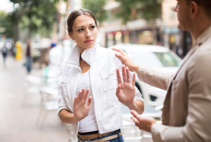 Portrait  of unhappy girl getting rid of unwelcome stranger outdoors