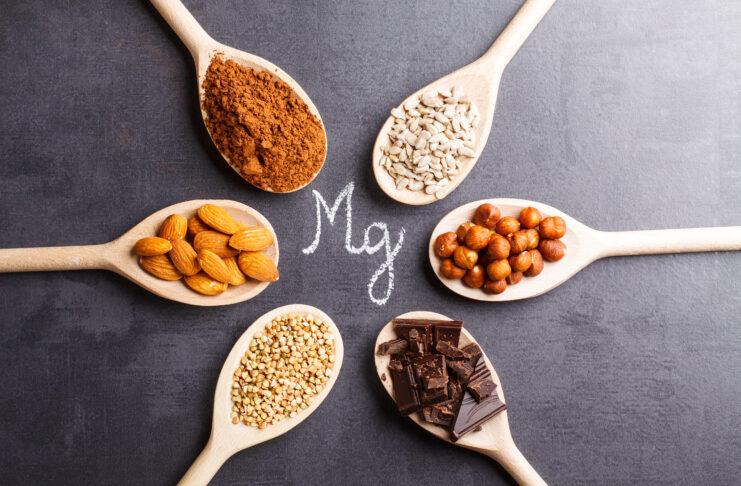 Magnesiumhaltige Produkte auf Holzlöffeln auf schwarzem Steinhintergrund.