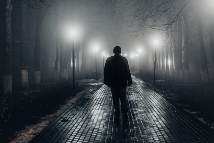 Sad man alone walking along the alley in night foggy park. Back view.