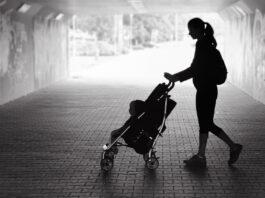 Samotna matka spacerująca w miejskim tunelu z dzieckiem w wózku.