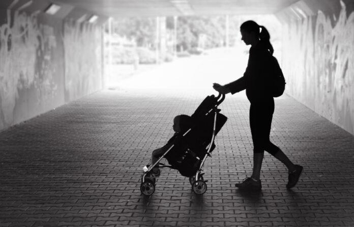 Alleenstaande moeder loopt in stadstunnel met baby in kinderwagen.