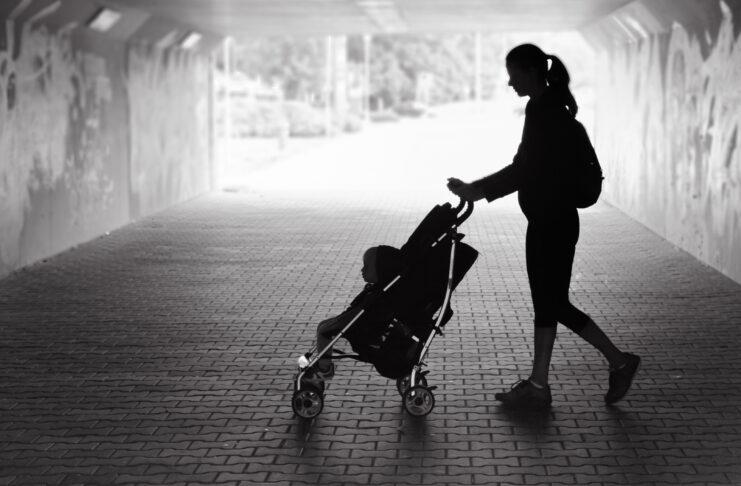 Alleinerziehende Mutter geht mit Baby im Kinderwagen durch einen Tunnel in der Stadt.