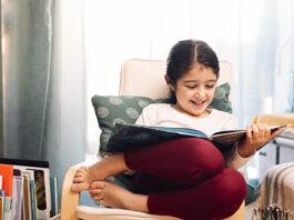 uśmiechnięta mała dziewczynka czytająca siedząc w domu, koncepcja wypoczynku w domu dla dzieci