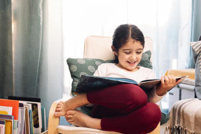 sorridente bambina che legge seduto a casa, concetto di tempo libero a casa per i bambini