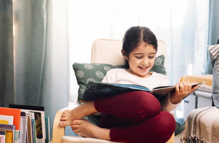 Lächelndes kleines Mädchen, das zu Hause sitzend liest, Konzept der Freizeitgestaltung zu Hause für Kinder