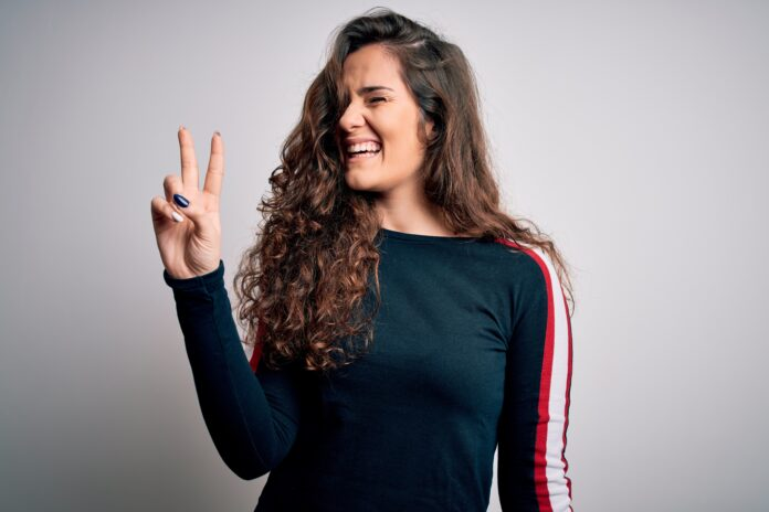 Young beautiful woman with curly hair wearing casual sweater over isolated white background smiling with happy face winking at the camera doing victory sign. Number two.