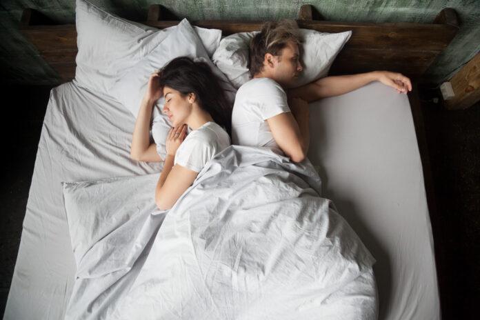 Jeune fille et jeune homme, couple dormant sous une couverture, dos à l'autre, dans une chambre à coucher à la maison, vue de dessus. Tôt le matin, paresseux dimanche week-end ou journée de sieste. Personnes se reposant à la maison