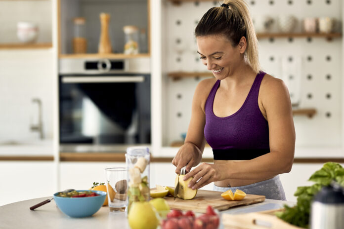 Young happy sportswoman slicing fruit while making smoothie in her kitchen.