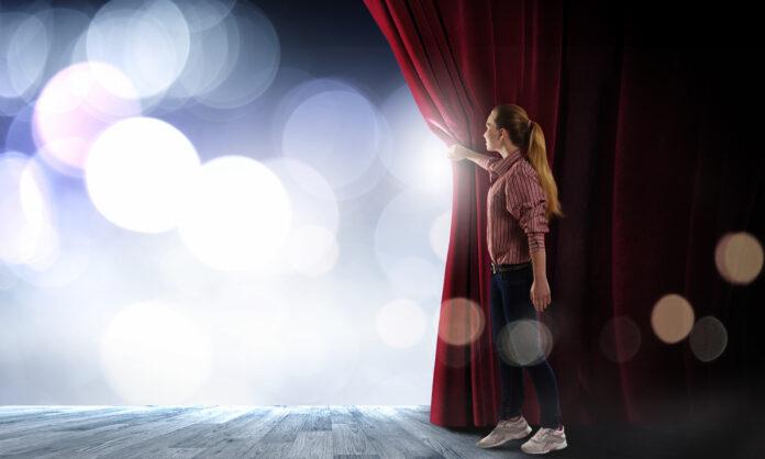 Junge Frau in legerer Kleidung beim Öffnen des Bühnenvorhangs