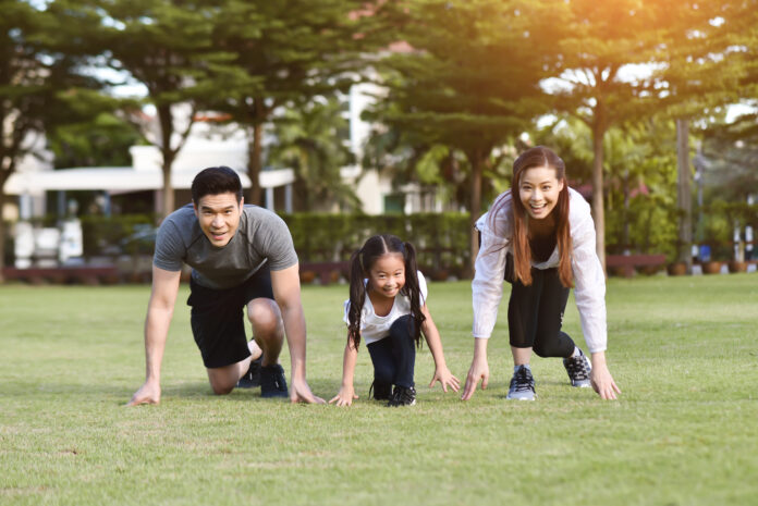 Asian family exercising at park outdoor. Mother, Father, Daughter getting ready to start on grass for running.