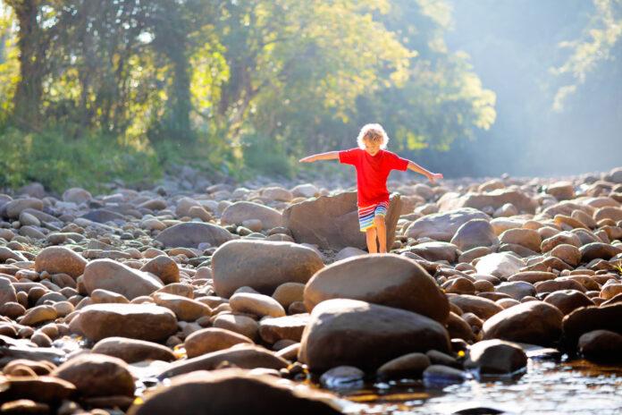 Bambini che fanno escursioni nelle montagne delle Alpi attraversando il fiume. Bambini giocano in acqua in montagna in Austria. Primavera vacanza in famiglia. Ragazzino sul sentiero di escursione. Divertimento all'aperto. Ricreazione attiva con i bambini.