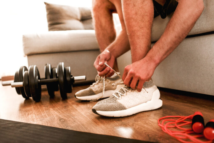 Close-up of laces on white sneakers at home. Guy get ready for workout at home.