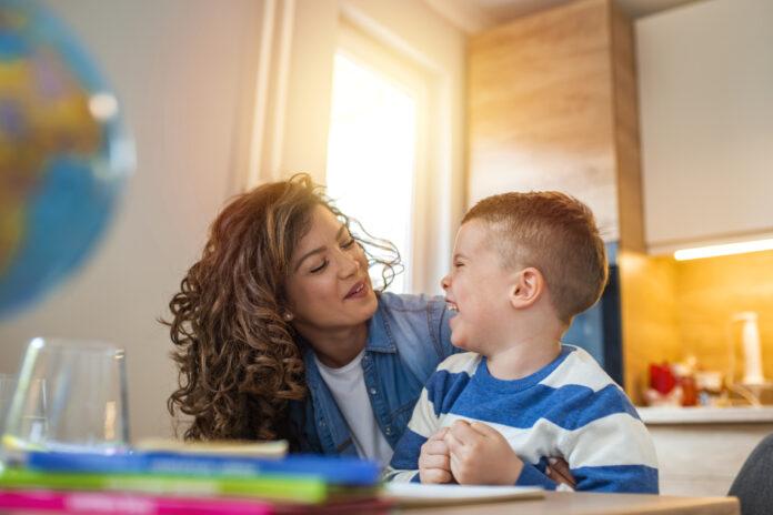 Mère aimable aidant son fils à faire ses devoirs dans la cuisine. Mère aidant son fils à faire ses devoirs à table. Créativité des enfants. Portrait d'une mère souriante aidant son fils à faire ses devoirs dans la cuisine à la maison.