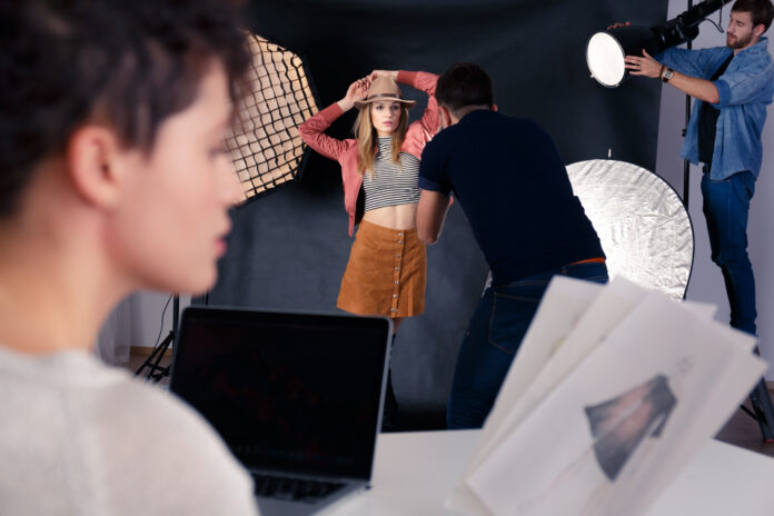 Photographer working with professional model during photo shoot