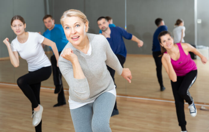 Portrait of emotional middle-aged woman doing exercises during group class in dance center