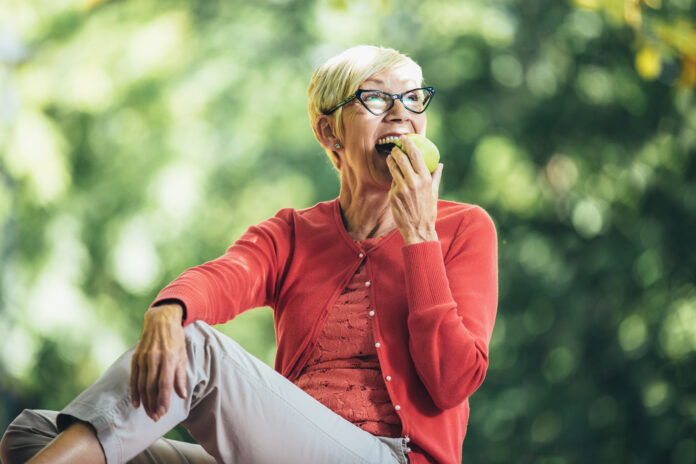 Portrait of senior woman at picnic in park eating green apple.