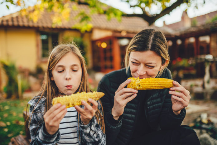 Portrait of two girls eating sweet corn outdoor