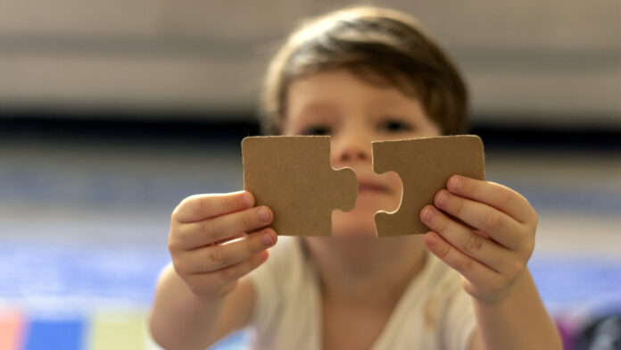Puzzles in the hands of a child on colorful background.Boy at home playing with puzzles.Cute little child connecting a jigsaw pieces.Portrait of toddler holding jigsaw puzzle block,looking at camera.