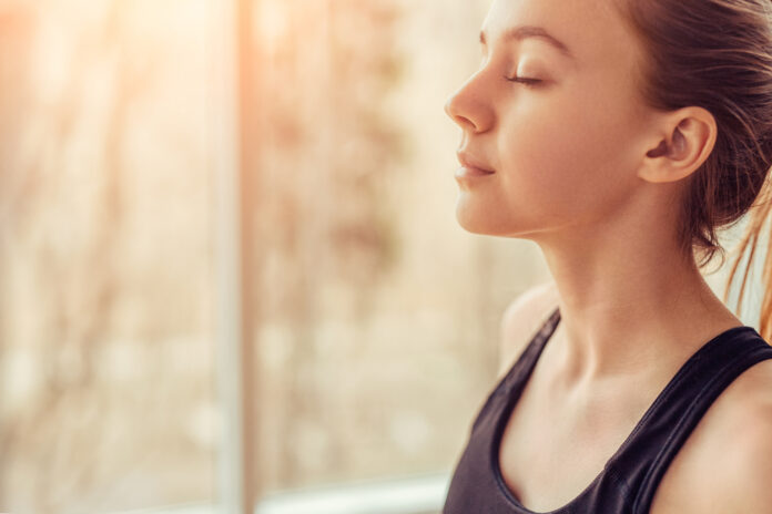 Seitenansicht einer jungen Frau mit geschlossenen Augen, die bei einer Atemübung während einer Yoga-Sitzung im Fitnessstudio tief durchatmet