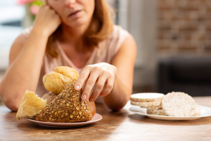 Taking little bun. Woman allergic to gluten taking little bun with seeds not gluten free crisps