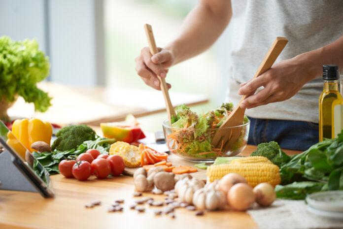 Vegetarian man mixing vegetable salad in bowl