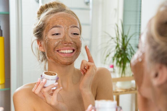 Young beautiful girl applying facial scrub mask on skin. Looking in the mirror in bathroom, Wrapped in a towel, having fun.