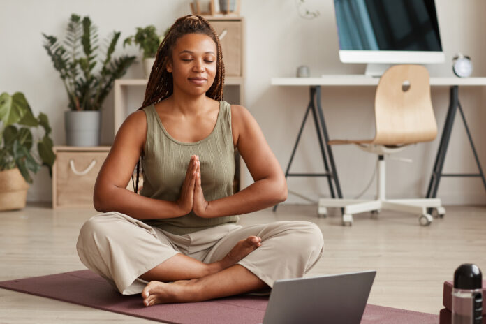 Young woman sitting in lotus position on exercise mat with her eyes closed and meditating in the living room