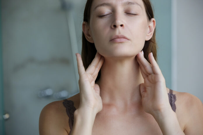 Young woman touching her throat. Sore throat, tonsillitis or thyroid gland problem.