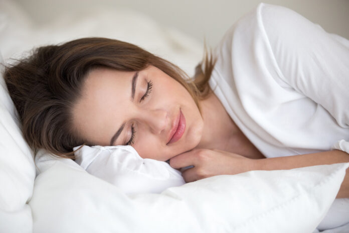 Jonge vrouw met mooi gezicht die goed op witte katoenen lakens en zacht kussen ligt te slapen in comfortabel gezellig bed thuis of hotel genietend van gezond dutje rustend genoeg voor goede ontspanning