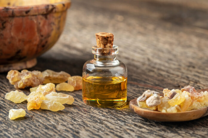A bottle of frankincense essential oil with frankincense resin crystals on a table