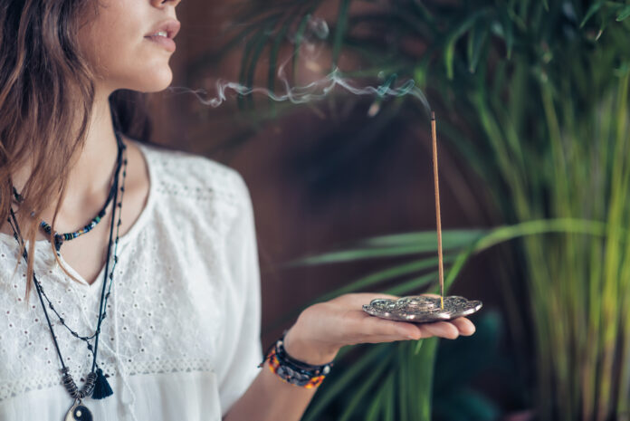 Beautiful mindfulness young girl relaxing and enjoying incense stick after yoga class.