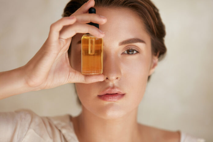 Beauty Face. Close Up Portrait Of Woman With Bottle Of Essential Oil. Beautiful Model With Radiant And Glowing Facial Skin Looking At Camera. Moisturizing With Serum Collagen And Hyaluronic Acid.