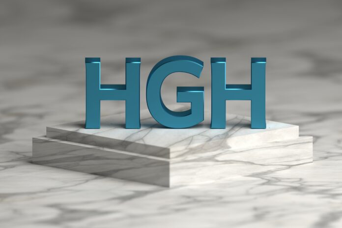 Bold blue letters HGH abbreviation of human growth hormone standing on marble pedestal.