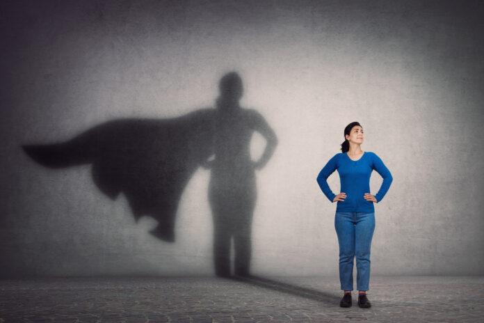 Odważna kobieta trzyma ręce na biodrach, uśmiecha się pewnie, rzucając na ścianę cień superbohatera z peleryną. Ambicja i koncepcja sukcesu w biznesie. Przywództwo bohater moc, motywacja i wewnętrzna siła symbol.