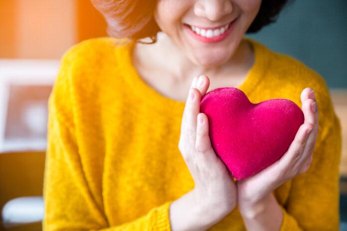 Nahaufnahme von Frau Hände in gelben Pullover hält rosa Herz. Menschen, Alter, Familie, Liebe, Valentinstag und Gesundheitsversorgung Konzept