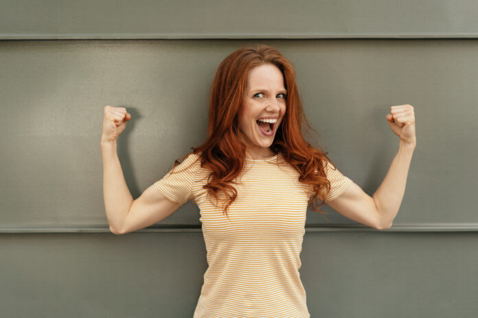 Funny young woman showing off her biceps clenching her fists in a power gesture while laughing at the camera