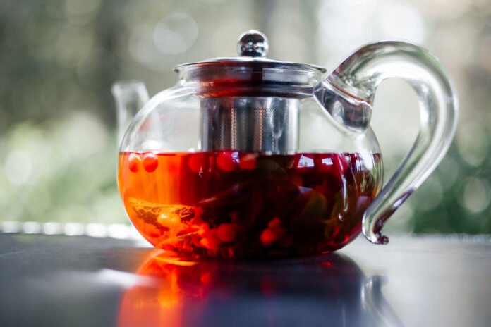 Glass teapot with hot red berry tea  , close-up
