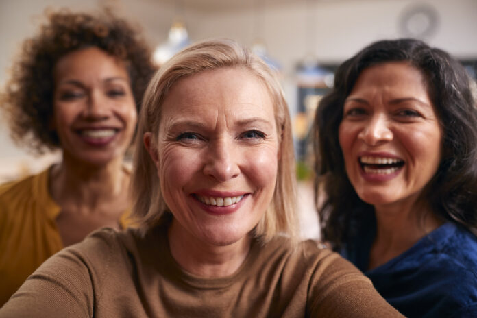 Group Of Mature Female Friends Posing For Selfie On Mobile Phone At Home
