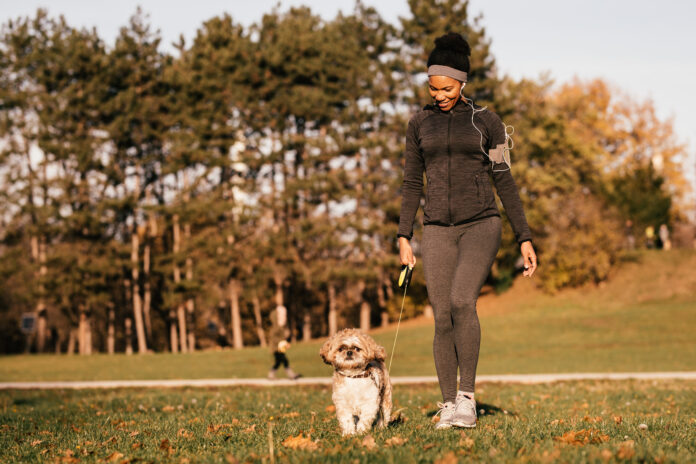 Happy black athletic woman walking with her dog in the park.