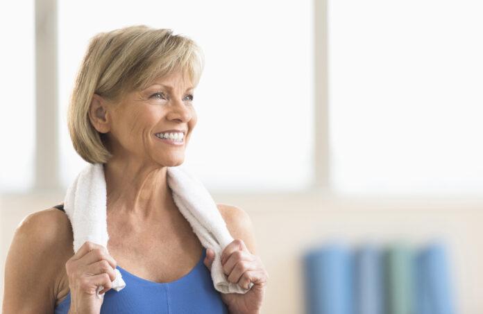 Glückliche reife Frau mit Handtuch um den Hals, die zu Hause wegschaut