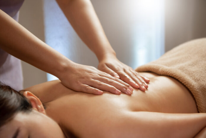 Masseuse doing massage on Asian female body in the spa salon. Beauty treatment concept. Enjoying and Relaxing.