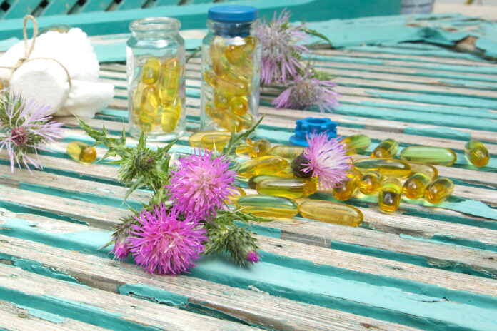 Milk thistle blossoms. Milk thistle oil in softgels in the background