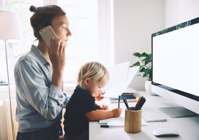 Modern mom balances between work and child home schooling on sick leave or quarantine. Mother works from home with kid. Woman responding on phone calls, working on computer with a toddler on her lap.