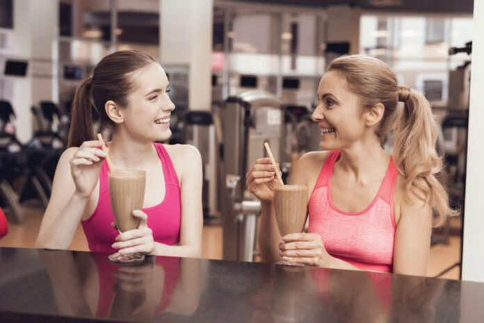 Mother and daughter in sportswear drinking protein shakes at gym. They look happy, fashionable and fit.