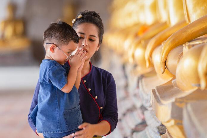 Mère et fils priant pour respecter la statue de Bouddha dans le temple Wat Phutthai Sawan, Ayutthaya, Thaïlande. Concept de la culture thaïlandaise