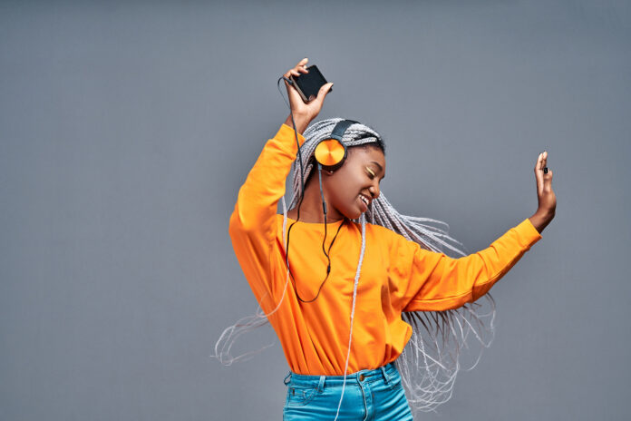 People, life, energy and music concept. Glad woman rejoices something, enjoys nice sound in new headphones, uses smartphone, listens song from playlist, spends time for dancing and entertaining. Isolated grey. Copy space