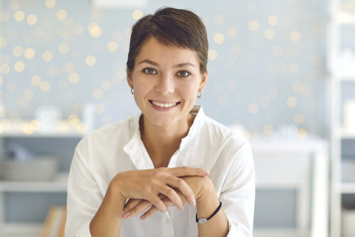 Portrait of happy lady with short haircut sitting in her home office smiling and looking at camera. Head shot of positive confident woman in smart casual clothes. Profile picture or webcam view